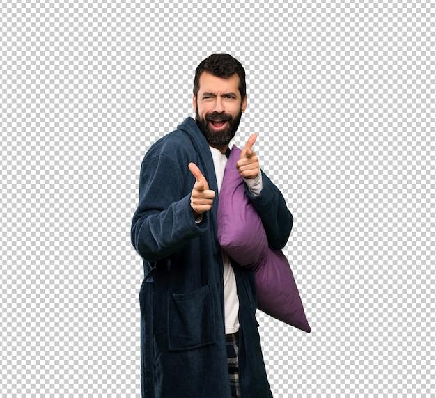 Homem com barba de pijama, apontando para a frente e sorrindo