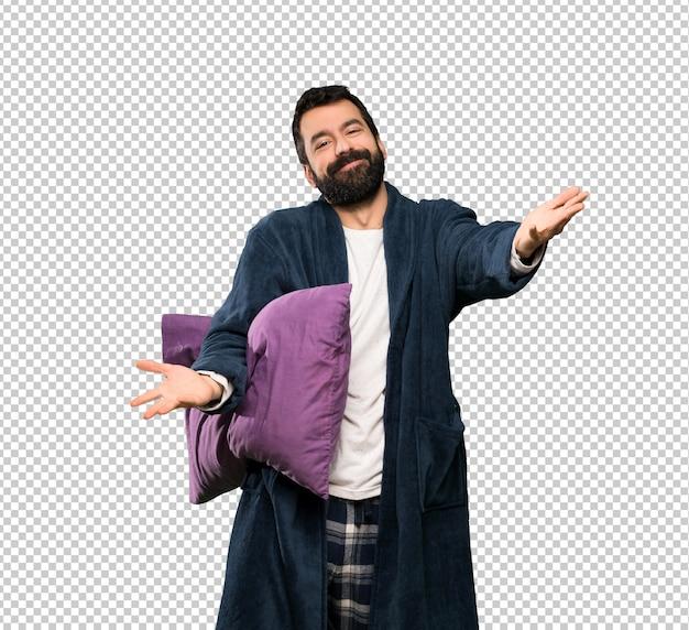 Homem com barba de pijama apresentando e convidando para vir com a mão