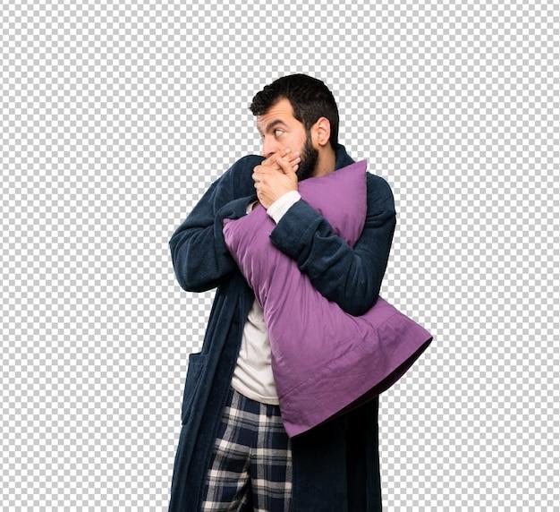 Homem com barba de pijama cobrindo a boca e olhando para o lado