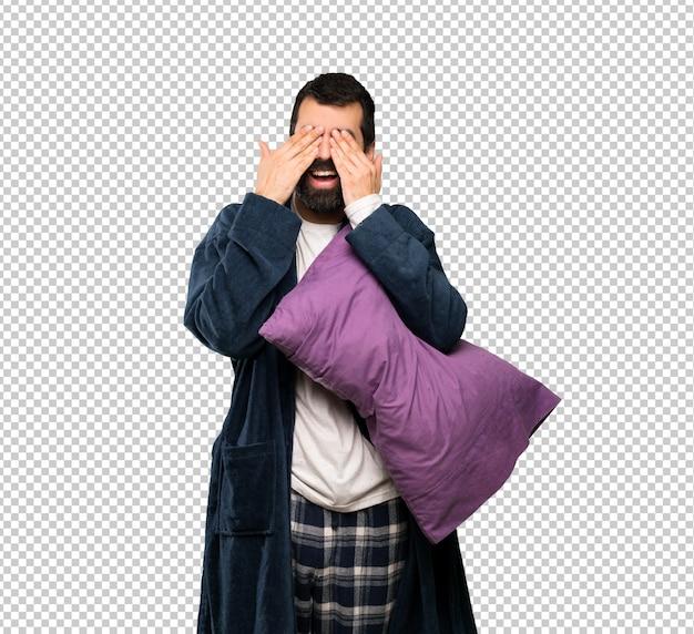 Homem com barba de pijama cobrindo os olhos pelas mãos