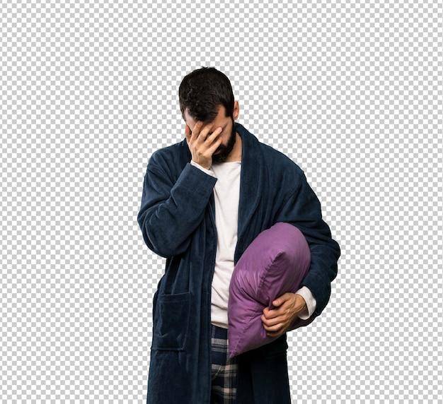 Homem com barba de pijama com expressão cansado e doente