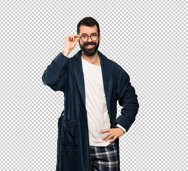 Homem com barba de pijama com óculos e surpreso