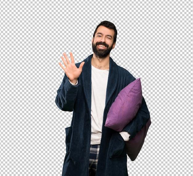 Homem com barba de pijama, contando cinco com os dedos