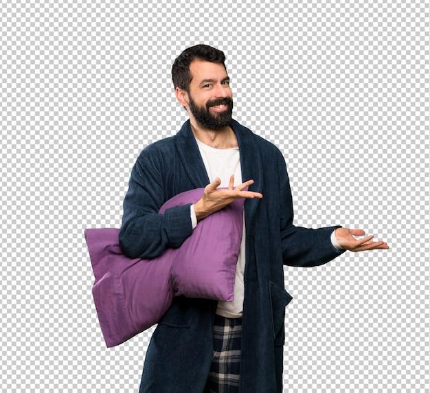 Homem com barba de pijama, estendendo as mãos para o lado para convidar para vir