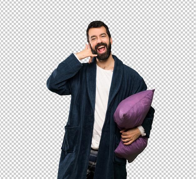 Homem com barba de pijama, fazendo o gesto do telefone. ligue para mim de volta
