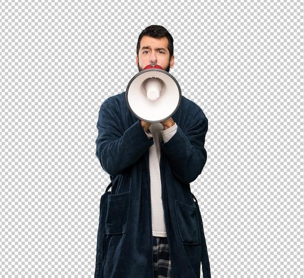 Homem com barba de pijama gritando através de um megafone