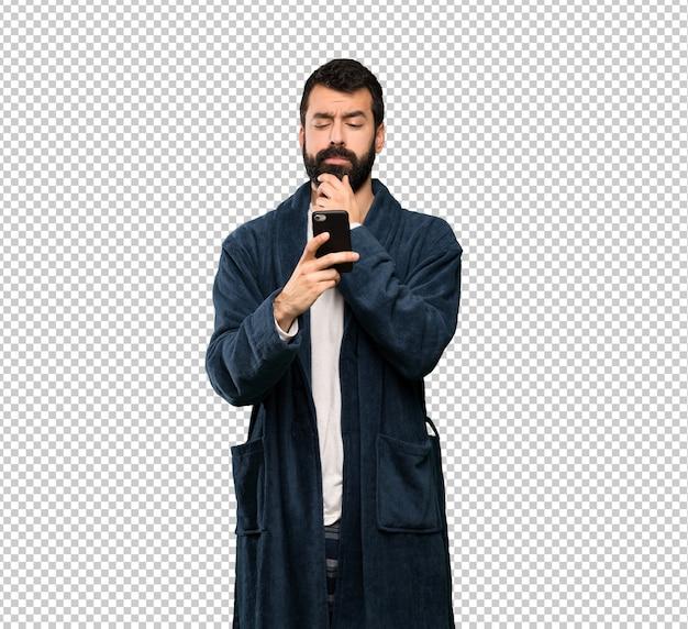 Homem com barba de pijama pensando e enviando uma mensagem