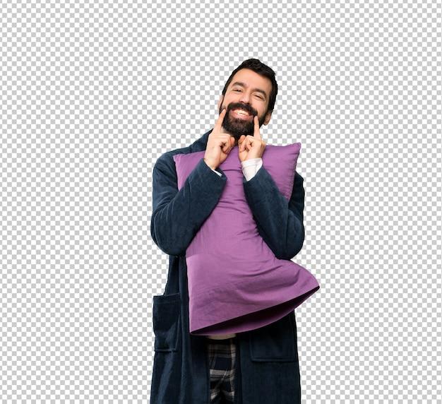 Homem com barba de pijama, sorrindo com uma expressão feliz e agradável