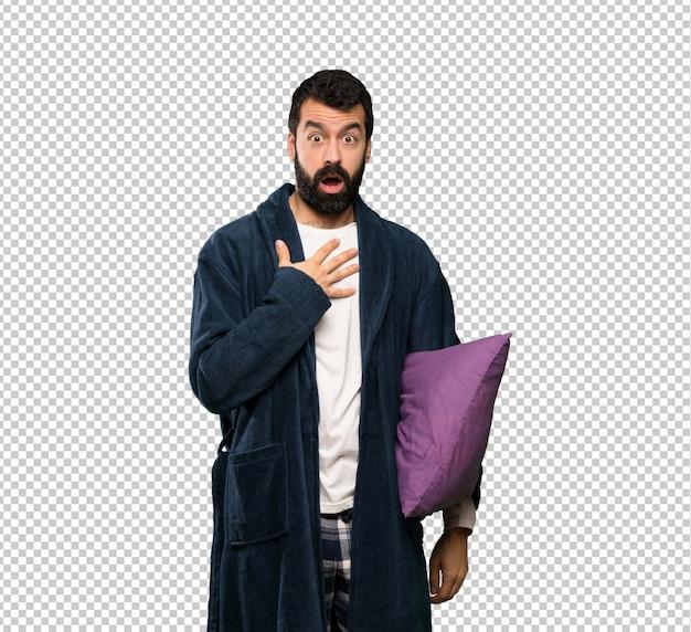 Homem com barba de pijama surpreso e chocado ao olhar para a direita