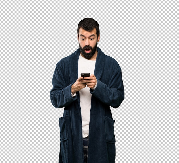 Homem com barba de pijama surpreso e enviando uma mensagem