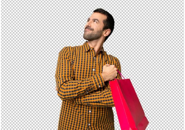 Homem, com, bolsas para compras, olhar, enquanto, sorrindo