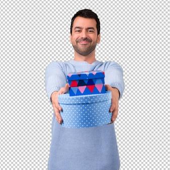 Homem com camisola azul segurando caixas de presente nas mãos