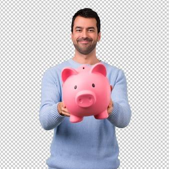 Homem com camisola azul, segurando um grande piggybank