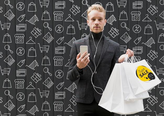 Homem com celular na mão e sacolas de compras
