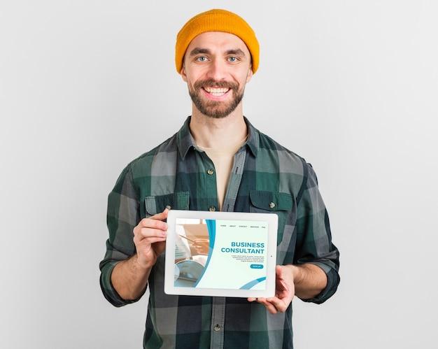 Homem com chapéu de inverno, segurando um tablet com landing page de negócios