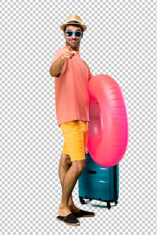 Homem com chapéu e óculos de sol em suas férias de verão aponta o dedo para você com uma expressão confiante