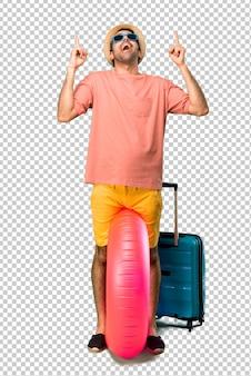 Homem com chapéu e óculos de sol em suas férias de verão, apontando com o dedo indicador uma ótima idéia e olhando para cima