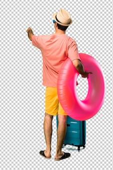 Homem com chapéu e óculos de sol em suas férias de verão, apontando para trás com o dedo indicador