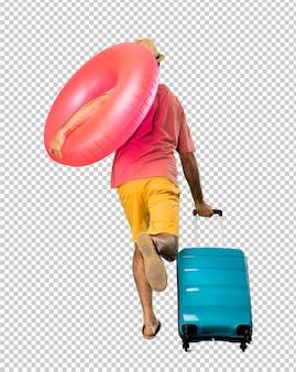 Homem com chapéu e óculos de sol em suas férias de verão correndo rápido
