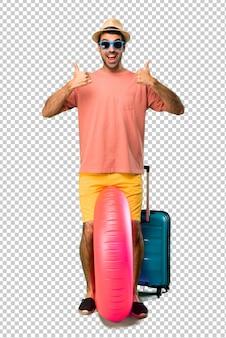 Homem com chapéu e óculos de sol em suas férias de verão dando um polegar para cima gesto e sorrindo porque teve sucesso