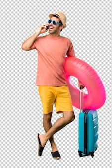 Homem com chapéu e óculos de sol em suas férias de verão falando ao celular