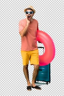 Homem com chapéu e óculos de sol em suas férias de verão, gritando com a boca aberta e anunciando algo