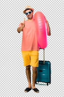 Homem com chapéu e óculos de sol em suas férias de verão mostrando e levantando um dedo no sinal dos melhores