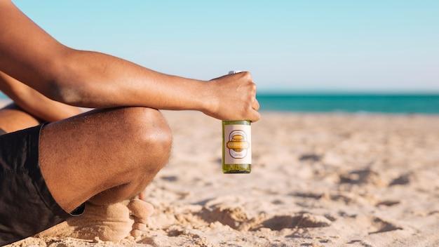 Homem com maquete de garrafa de cerveja na praia