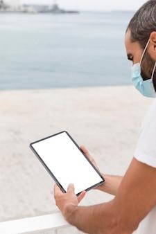 Homem com máscara na rua com tablet lendo online
