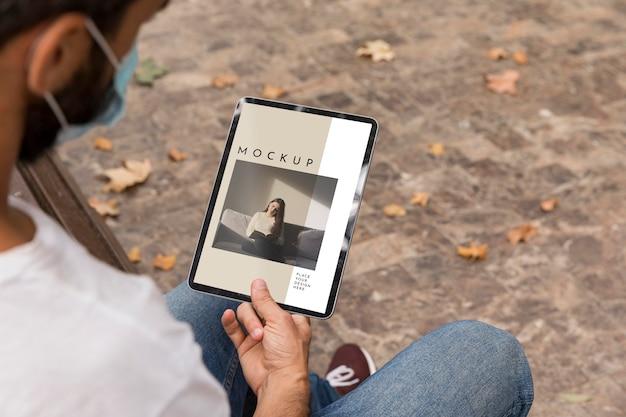 Homem com máscara na rua lendo livro no tablet