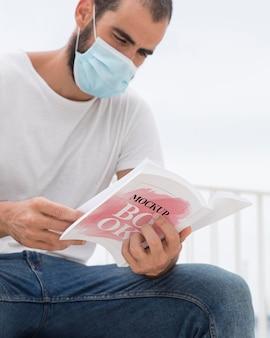Homem com máscara na rua lendo livro