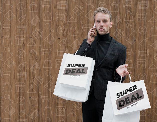 Homem com sacolas de compras falando telefone aver