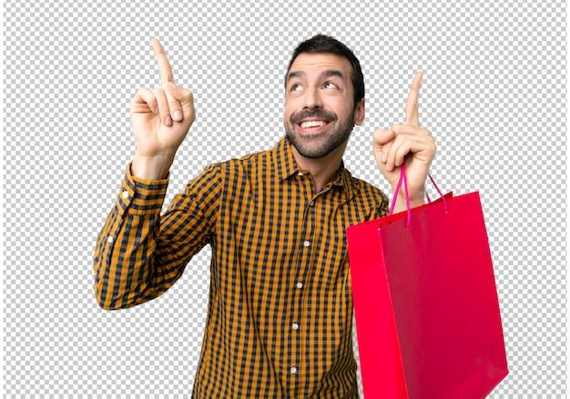 Homem com sacos de compras, apontando com o dedo indicador uma ótima idéia