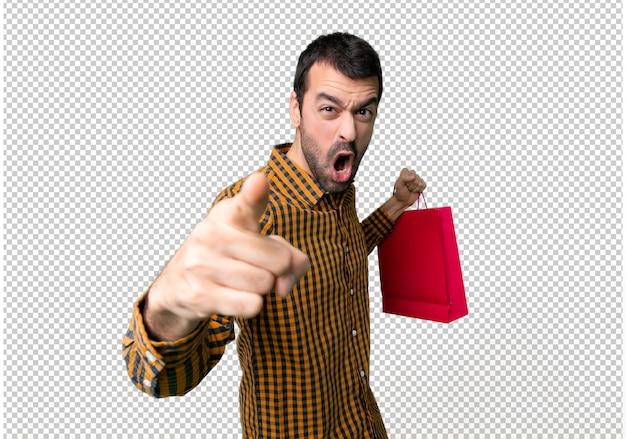 Homem com sacos de compras frustrados por uma situação ruim e apontando para a frente