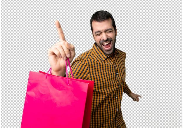 Homem com sacos de compras gosta de dançar enquanto ouve música em uma festa