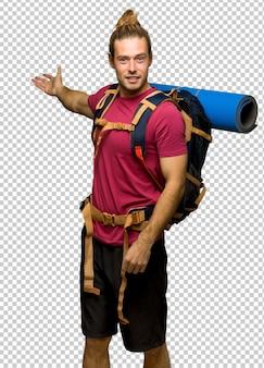 Homem de alpinista com mochileiro de montanha apontando para trás e apresentando um produto