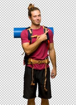 Homem de alpinista com mochileiros de montanha, apontando para o lado para apresentar um produto