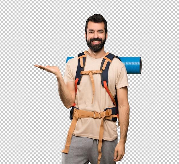Homem de alpinista segurando copyspace imaginário na palma da mão para inserir um anúncio