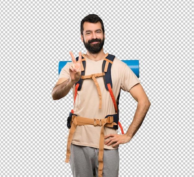 Homem de alpinista sorrindo e mostrando sinal de vitória