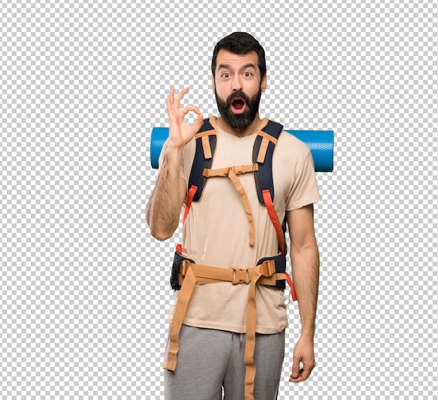 Homem de alpinista surpreso e mostrando sinal de ok