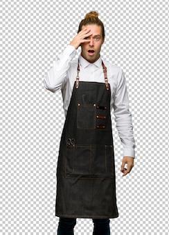 Homem de barbeiro de avental com surpresa e expressão facial chocada