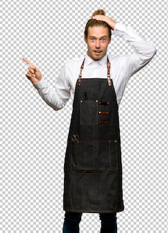Homem de barbeiro em um avental, apontando o dedo para o lado e apresentando um produto