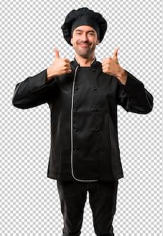 Homem de chef de uniforme preto, dando um polegar para cima gesto e sorrindo porque teve sucesso