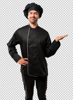 Homem de chef de uniforme preto segurando copyspace imaginário na palma da mão para inserir um anúncio