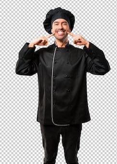 Homem de chef de uniforme preto, sorrindo com uma expressão feliz e agradável