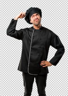 Homem de chef de uniforme preto, tendo dúvidas e com expressão de rosto confuso enquanto coçando a cabeça