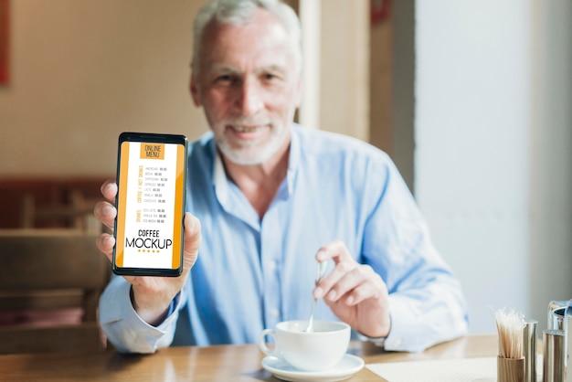 Homem de frente para a cafeteria segurando uma maquete de celular