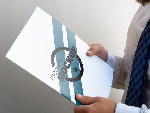 Homem de lado segurando uma maquete de caderno