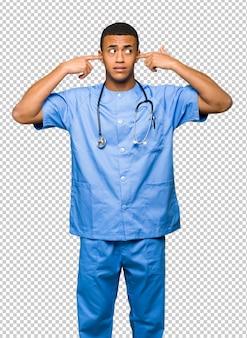 Homem de médico cirurgião cobrindo ambas as orelhas com as mãos