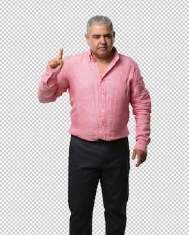 Homem de meia idade, mostrando o número um, símbolo da contagem, de matemática, confiante e alegre